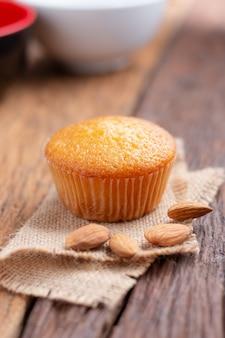 Bouchent une tasse de gâteau aux amandes contre le tissu de sac sur la table en bois