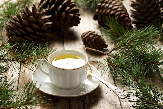 Bouchent le thé vert dans une tasse en porcelaine sur table en bois