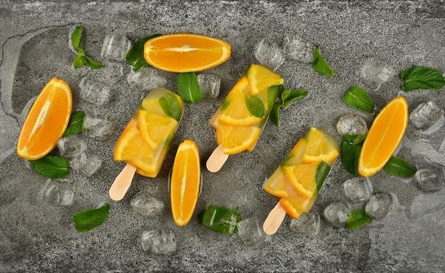 Bouchent trois sucettes glacées aux fruits avec des tranches d'orange fraîche, des feuilles de menthe verte et des glaçons sur la surface de la table grise, vue de dessus surélevée, directement au-dessus