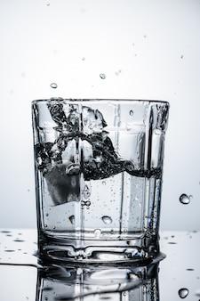 Bouchent le verre d'eau avec des glaçons et des gouttes sur fond clair.