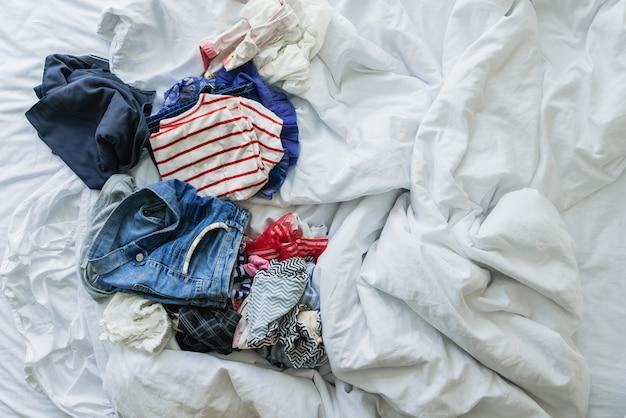 Bouchent les vêtements et les accessoires jetés sur le lit défait