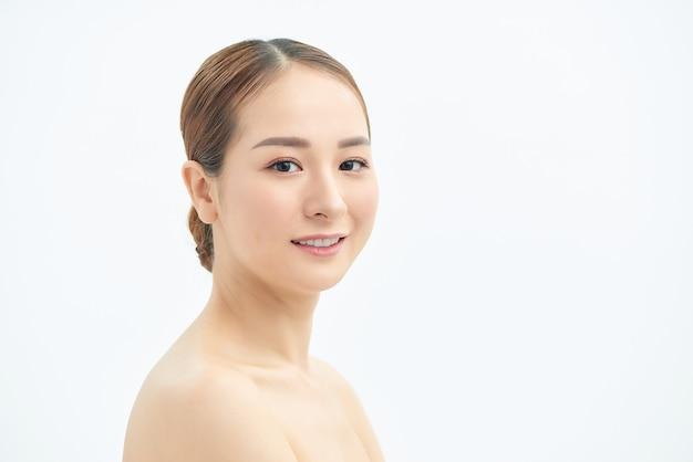 Bouchent le visage de la belle jeune femme asiatique sur fond blanc. concept spa et peau.