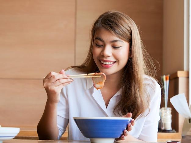 Bouchent le visage de la femme asiatique heureuse à l'aide de baguettes pour manger des nouilles au restaurant, concept de temps de déjeuner.