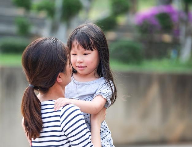 Bouchent le visage de petite fille heureuse dans les bras de sa mère.