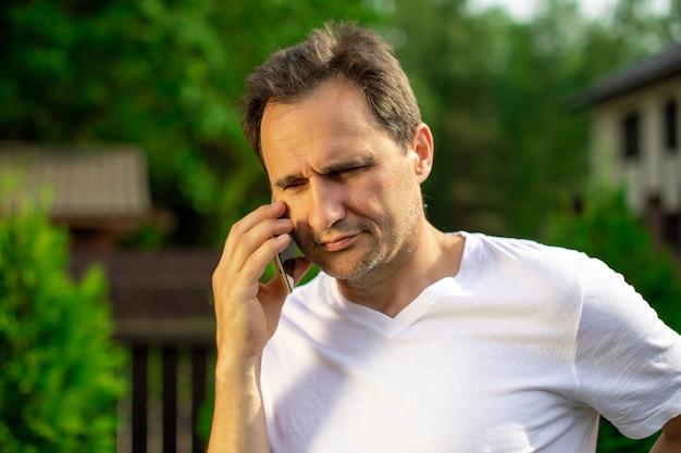 Bouchent la vue de bel homme confiant parlant au téléphone mobile à l'extérieur. homme d'affaires faisant un appel téléphonique, appelant sur smartphone. copiez l'espace, l'été, la communication, les gens, le concept de gadgets numériques