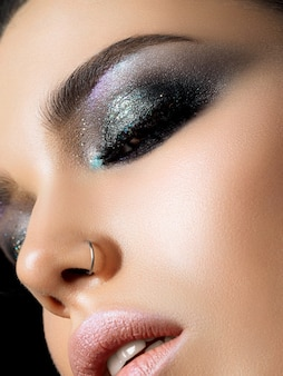 Bouchent la vue de la belle jeune femme avec une peau parfaite et un maquillage de soirée