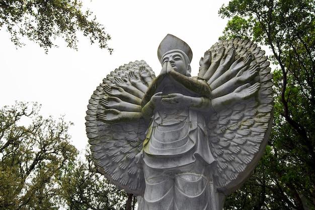 Bouchent la vue d'une belle statue de bouddha sur un parc.
