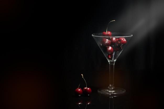 Bouchent la vue de la cerise dans un verre à martini dans un fond noir avec fusée et avant-plan.