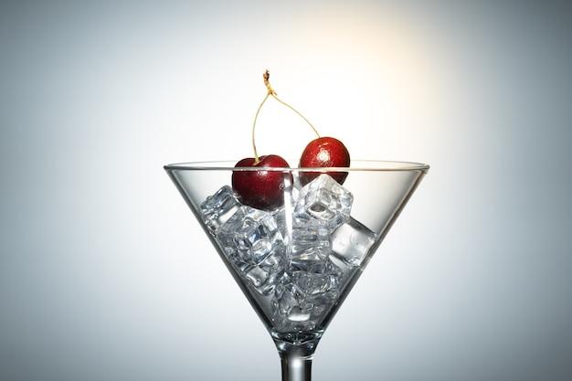 Bouchent la vue de la cerise parmi les glaçons dans un verre à martini sur fond blanc avec fusée.