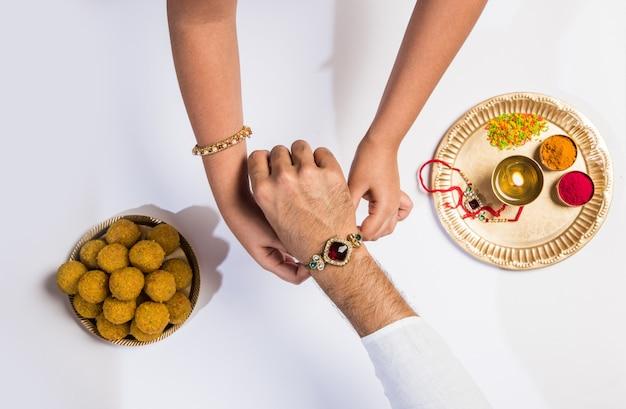 Bouchent la vue de dessus des mains féminines attachant des rakhi colorés sur la main de son frère isolé sur fond blanc lors du festival raksha bandhan