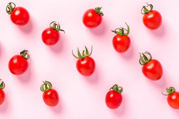 Bouchent la vue de dessus de tomates cerises mûres fraîches sur rose pastel