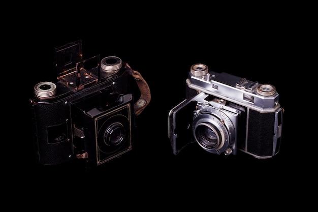 Bouchent la vue de deux appareils photographiques vintage rétro isolés sur fond noir.