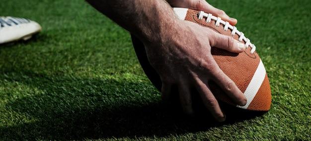 Bouchent la vue du joueur de football américain se préparant pour un coup de pied de baisse