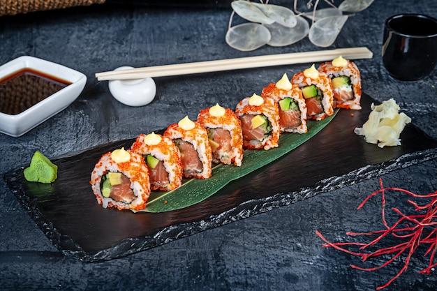 Bouchent la vue sur l'ensemble de rouleaux de sushi. rouleau de californie au saumon, avocat et caviar servi sur pierre noire sur fond sombre. cuisine japonaise. copiez l'espace. sushi servi pour le menu. nourriture saine, fruits de mer