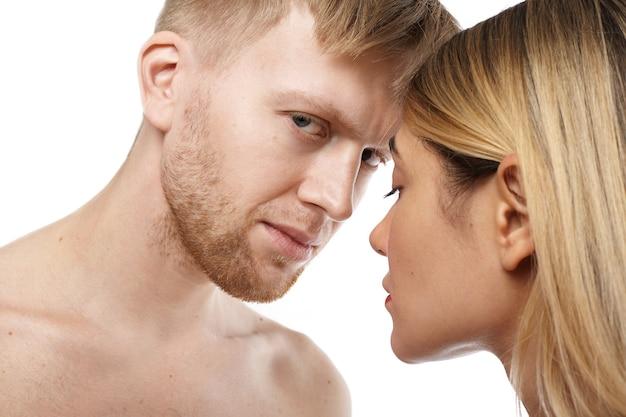Bouchent la vue isolée du mec caucasien mal rasé torse nu attrayant va faire l'amour à la belle femme blonde tendre. couple adulte posant nu, étreignant et s'embrassant. sexe et sensualité