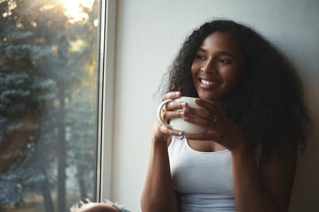 Bouchent la vue de la jolie jeune femme afro-américaine à la mode en débardeur blanc se reposer à l'intérieur, tenant une grande tasse de thé chaud, souriant largement, rêvasser, passer du bon temps seul à la maison