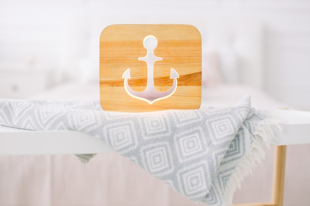 Bouchent la vue de la lampe de nuit en bois confortable avec une image découpée d'ancre, sur une couverture grise à l'intérieur de la chambre lumineuse confortable