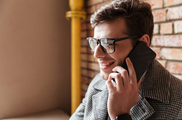 Bouchent la vue latérale de l'homme d'affaires heureux à lunettes