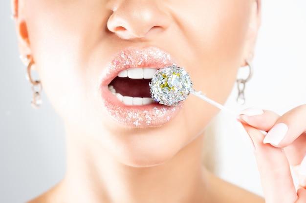Bouchent la vue des lèvres de la belle femme avec une sucette festive.