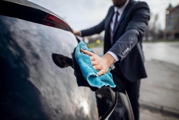 Bouchent la vue de la main de mise au point de l'élégant barbu beau jeune homme travailleur en costume nettoyage de la fenêtre avec un chiffon en microfibre bleu sur la station de lavage de voiture en libre-service manuel.
