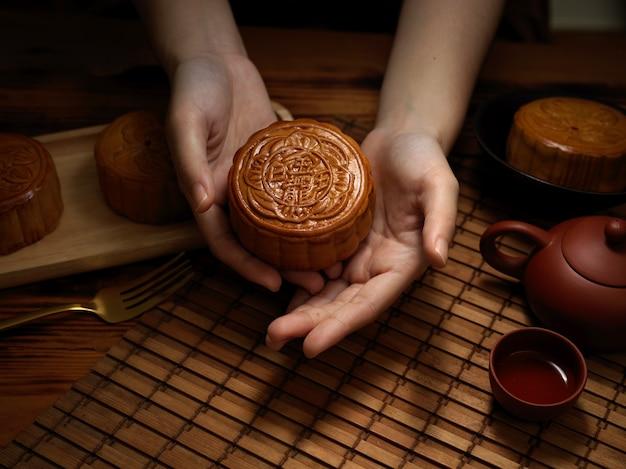 Bouchent la vue des mains féminines tenant le gâteau de lune au-dessus de la table au festival de la lune. le caractère chinois sur le gâteau de lune représente