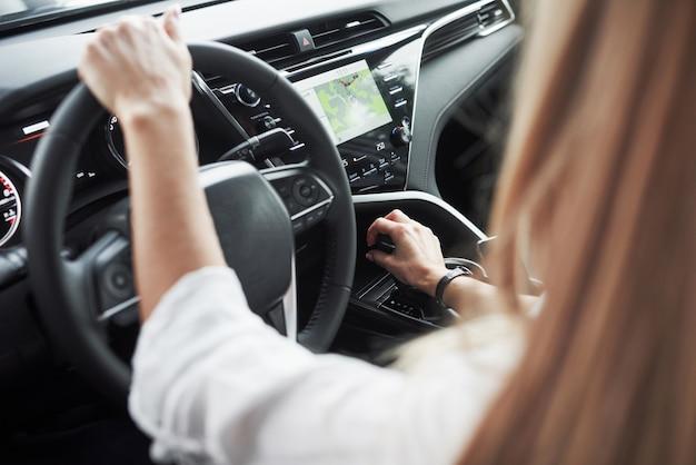 Bouchent la vue des mains de la femme dans la belle voiture moderne de couleur noire
