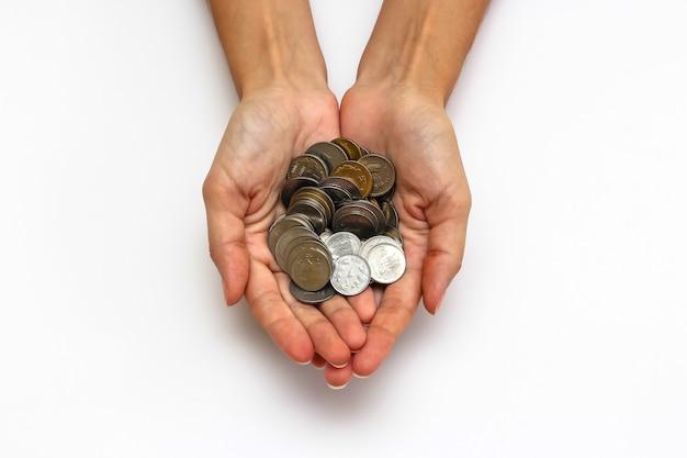 Bouchent la vue des mains de la femme avec des pièces de monnaie de roupies indiennes sur fond blanc.