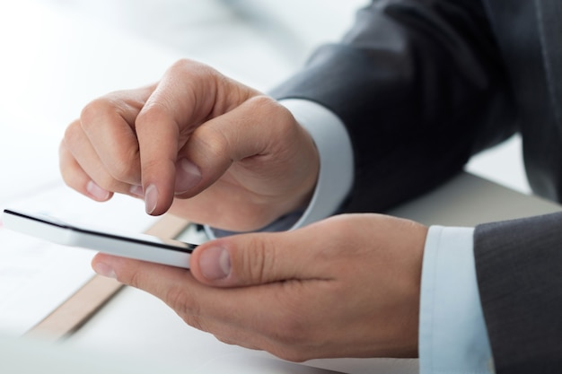 Bouchent la vue des mains d'homme d'affaires tenant un téléphone intelligent. applications mobiles, jeux, médias sociaux, organisation du travail, banque en ligne ou concept d'achat.