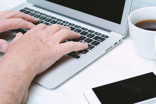 Bouchent la vue des mains senior sur le clavier avec une tasse de café un téléphone.