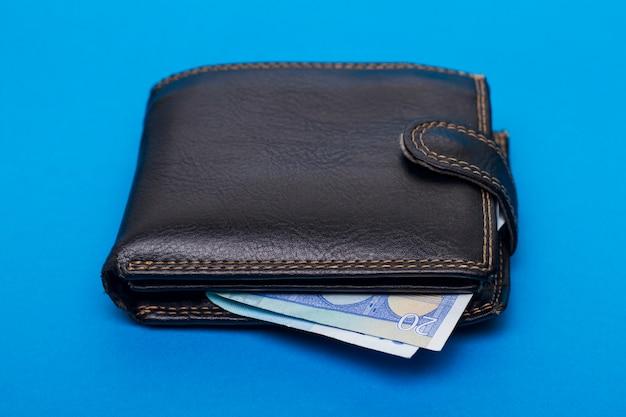 Bouchent la vue d'un portefeuille d'argent de poche sur un fond bleu.