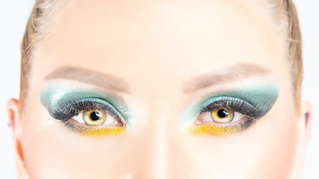 Bouchent la vue des yeux de belle femme avec un maquillage lumineux.