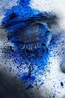 Bouchent les yeux d'une fille mannequin avec du maquillage en poudre colorée.