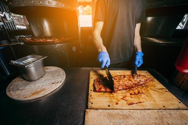 Le boucher ou le chef masculin prépare des steaks de côte de bœuf à partir d'un gros rôti de côte de bœuf