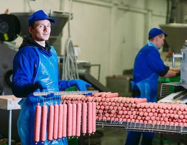 Bouchers transformant des saucisses à une usine de viande.