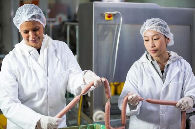 Bouchers transformant des saucisses