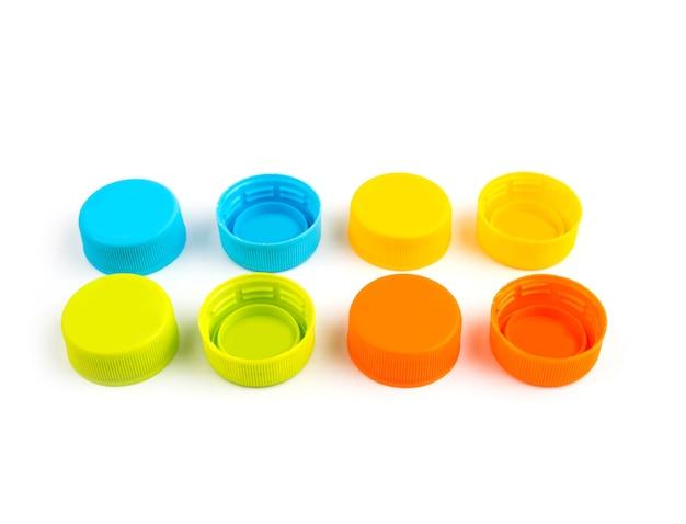 Bouchons de bouteilles en plastique coloré sur fond blanc. mise au point sélective