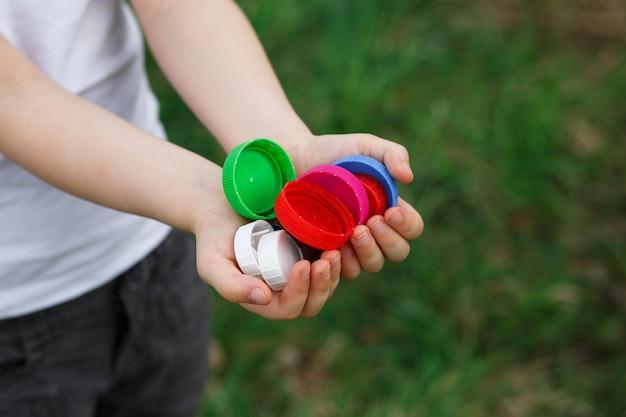Bouchons de bouteilles en plastique dans les mains des enfants