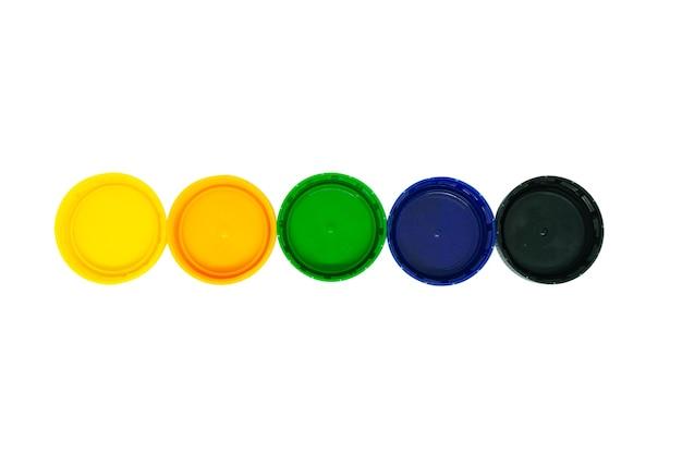Bouchons en plastique jaune, orange, vert, bleu et noir isolés sur fond blanc.