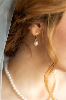 Boucle d'oreille de perle de mariage sur l'oreille de la jeune mariée