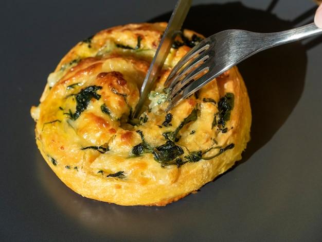 Une boucle de pâte aux épinards et au fromage est coupée avec un couteau et une fourchette.