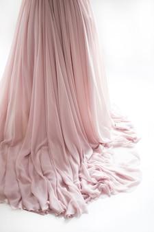 Boucle d'une robe de mariée sur un sol. ourlet de robe de mariée, studio, fond clair