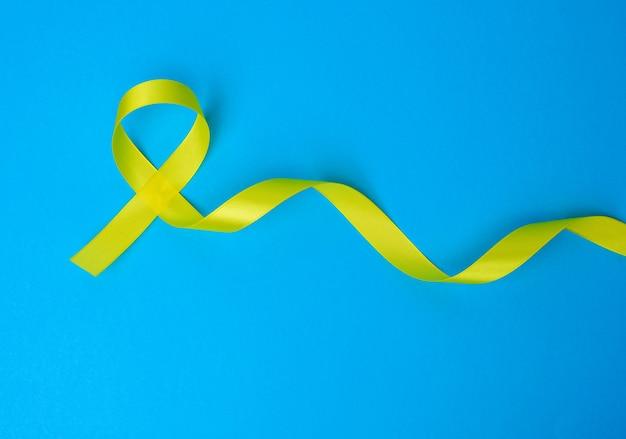 Boucle de ruban de soie jaune sur fond bleu. sensibilisation au cancer des os de sarcome, vue de dessus