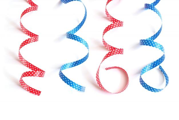 Bouclés bleus et rouges avec des rubans à pois blancs isolés sur blanc