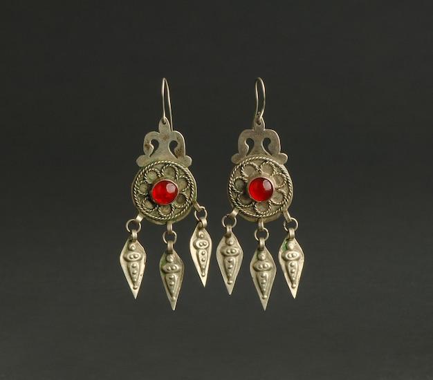 Boucles d'oreilles antiques antiques avec des pierres sur fond noir. bijoux vintage d'asie centrale