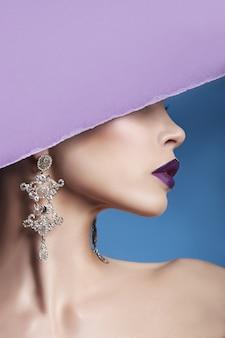 Boucles d'oreilles et bijoux à l'oreille d'une femme sexy pressée contre le papier violet. fille brune parfaite, magnifique look mystérieux. bijoux publicitaires, belles boucles d'oreilles à l'oreille de la fille. espace copie