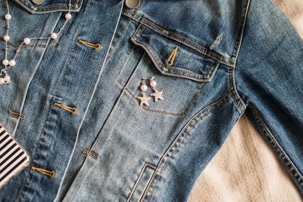 Boucles d'oreilles faites à la main se trouvent sur une veste en jean