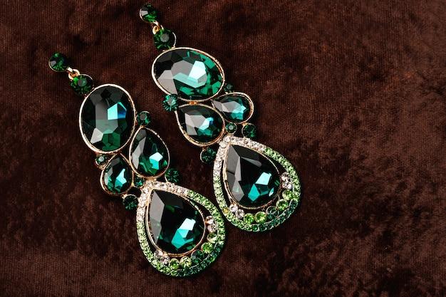 Boucles d'oreilles de luxe avec pierres vertes sur le velours marron
