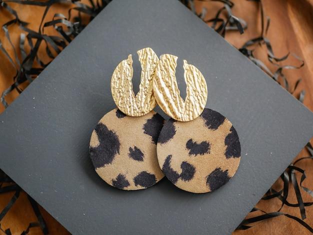 Des boucles d'oreilles en or. bijoux pour femmes. fond de décoration vintage. belles broches, bracelets, colliers et boucles d'oreilles aux tons dorés sur un plateau en bois. mise à plat, vue de dessus