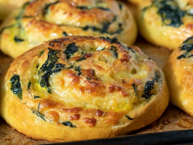 Boucles de pâte aux épinards et au fromage sur une plaque à pâtisserie. vue de côté