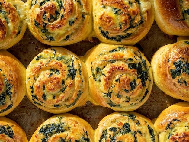 Boucles de pâte aux épinards et au fromage sur une plaque à pâtisserie. vue de dessus